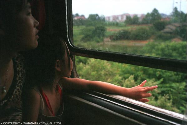 车上一名小女孩把手伸出窗外乘凉。(D4111)