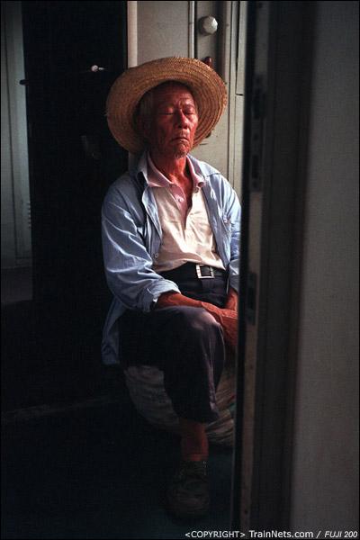 过道上坐着行李的老人。(D4114)