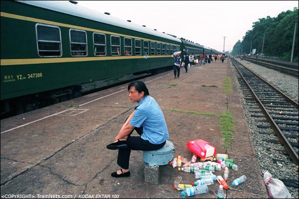 一位列车员坐在站台上休息,身后是来时清理的罐子。(D4208)