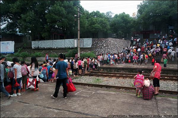 乘客下车后涌向通往出站口的小道口,排起了长长的人龙。(D3919)