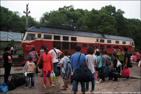 本务机换向后开往车首,出站的乘客自觉地在小道口前等待。(D3925)