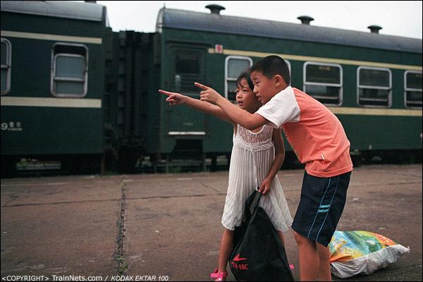 一对小兄妹在站台上等待亲人来接。(D3933)