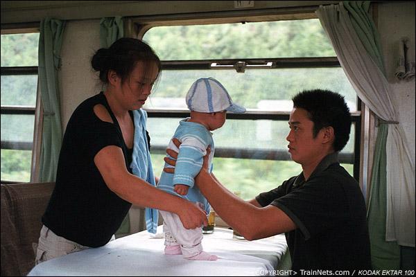 餐车上位置比较松动,一对夫妇在餐桌上玩孩子。(D4102)