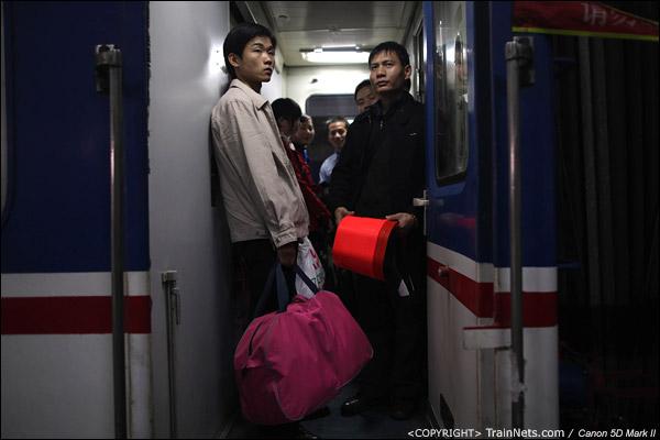 2011年1月27日,深圳站。前往武昌的列车,门端占满了人,一名乘客拿着红色的小板凳准备关门时占位置。(IMG-0629-110127)