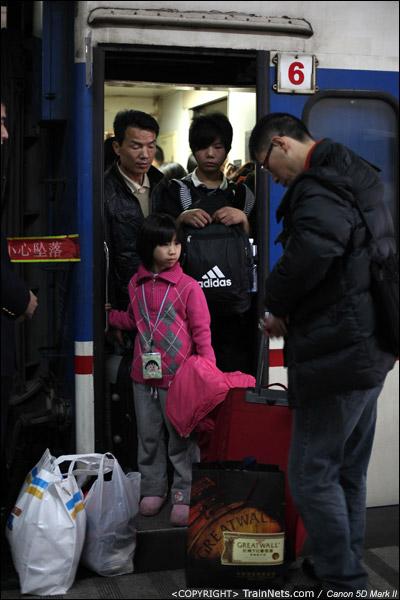2011年1月27日,深圳。前往武昌的列车,补票车厢的门端已经挤满了人,一名父亲正在整理行李,准备带着孩子挤进去。(IMG-0707-110127)