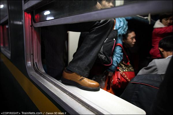 2013年1月28日。深圳西站。L6次深圳西-成都,一位卧代座的乘客因为拥挤,脚踏上了小桌板。(IMG-5281-130128)