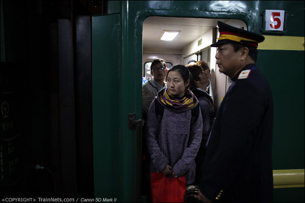 2011年1月26日,深圳西站。前往达州的列车,门端已经挤得站不下,一名站在门边的女乘客探头张望。(IMG-5786-110116)