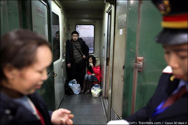2011年1月18日。深圳站。前往成都的列车,坐在门端的一对情侣看着列车员在交接工作。(IMG-6833-110118)