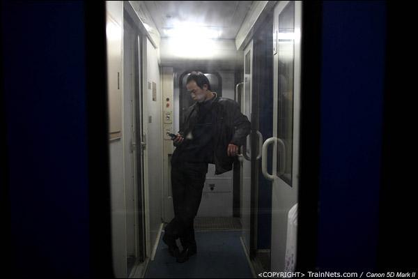 2011年1月20日,深圳站。前往武昌的列车,一名乘客找到了较空的门端,休闲地发着短信。(IMG-8066-110120)