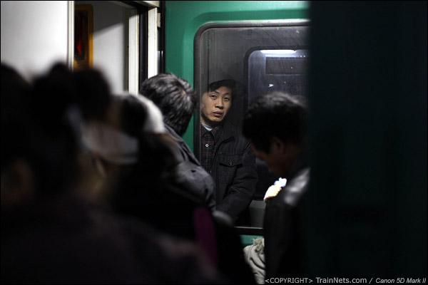 2011年1月22日,深圳西。前往达州的列车,一名乘客透过连接处的车门窗户,看着往上挤的乘客。(IMG-8996-110122)