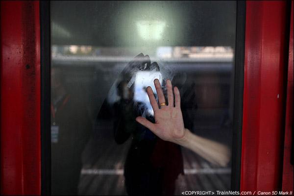 2011年1月25日,深圳站。前往九江的列车,因为门端太拥挤,一名乘客伸手扶着窗户。(IMG-9756-110125)