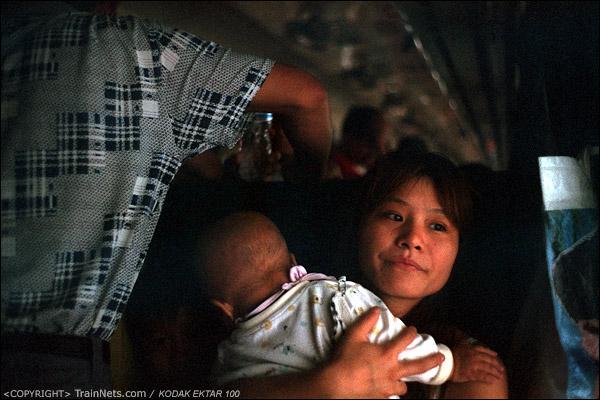 一位母亲抱着孩子在窗边吹风。(D3728)