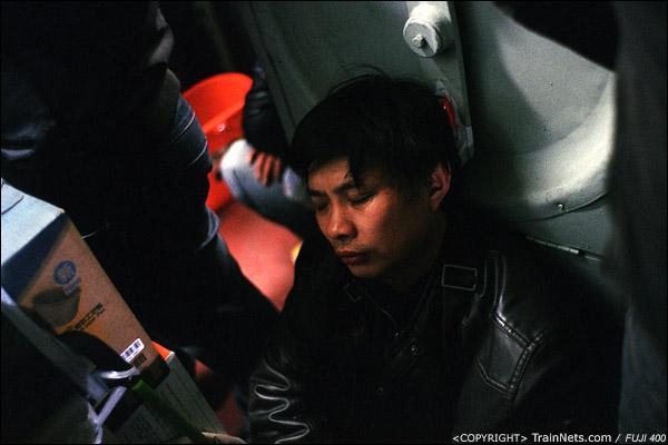 15号车厢,一位乘客坐在门端熟睡。(D7319)