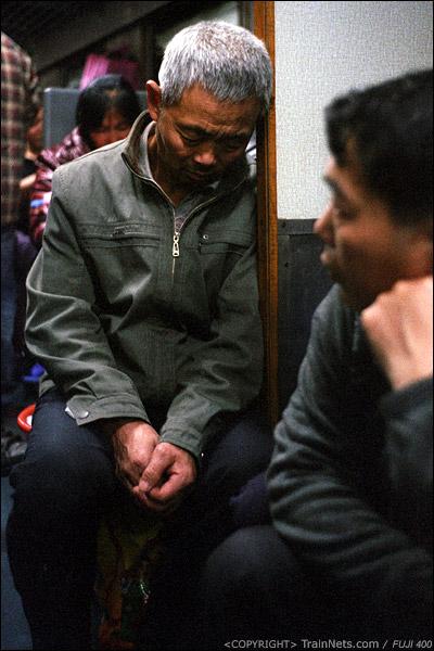 14号车厢,一位乘客头靠着洗手池间墙壁熟睡。(D7327)