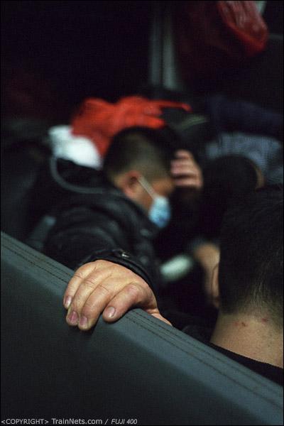 14号车厢,一位乘客右手拉着座椅靠背,左手托着头趴在桌子上睡觉。(D7329)