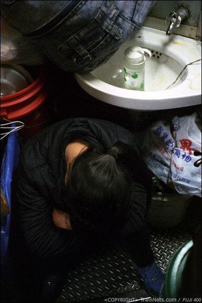13号车厢,一位乘客坐在洗手池下方熟睡。(D7336)