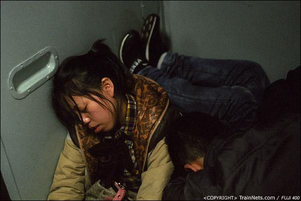 13号车厢门端,一位乘客靠在墙上睡觉,头后面则是另一位乘客的脚。(D7403)