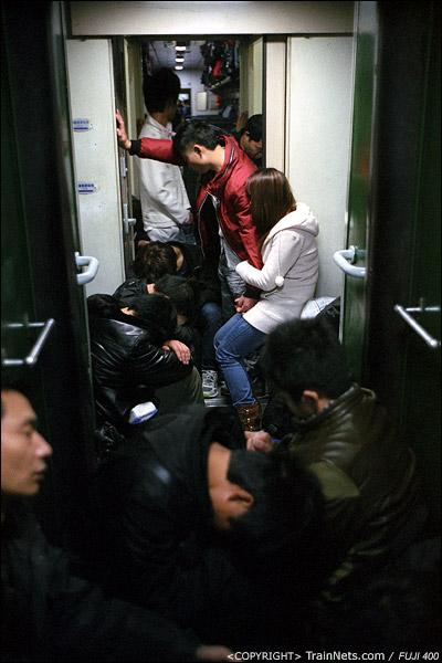 12、13号车厢连接处挤满了席地而睡的乘客。(D7410)
