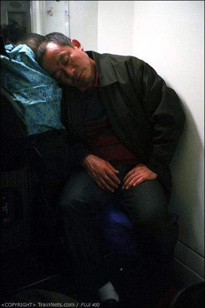 12号车厢,一位乘客坐在洗手池旁睡觉。(D7412)