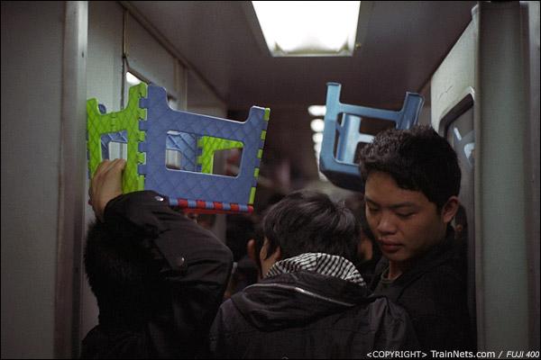 12号车厢,乘客纷纷举起小板凳,让卖货的小推车通过。(D7419)