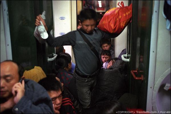12号车厢连接处,一位乘客在人群中穿行。(D7421)