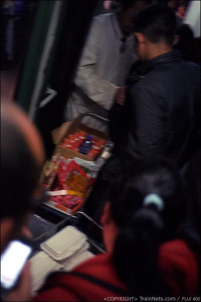 12、13号车厢连接处,卖小吃和卖饭的小推车在风挡处交汇。两车强行在人群中通过。(D7423)
