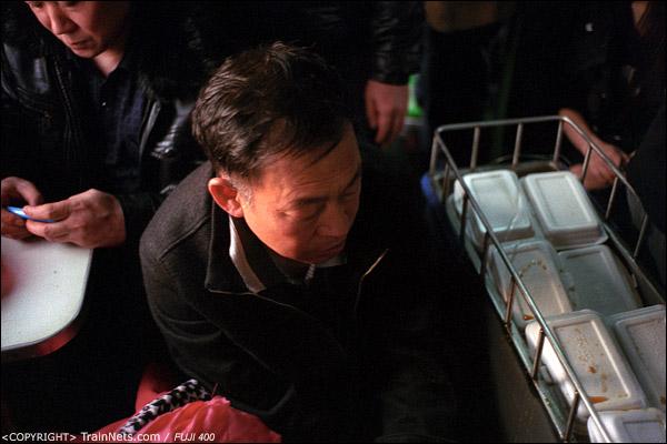 13号车厢,卖饭的小推车在一位无座乘客脸旁推过。(D7424)