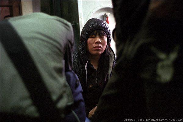 12号车厢门端,一位乘客在半睡半醒的状态。(D7426)