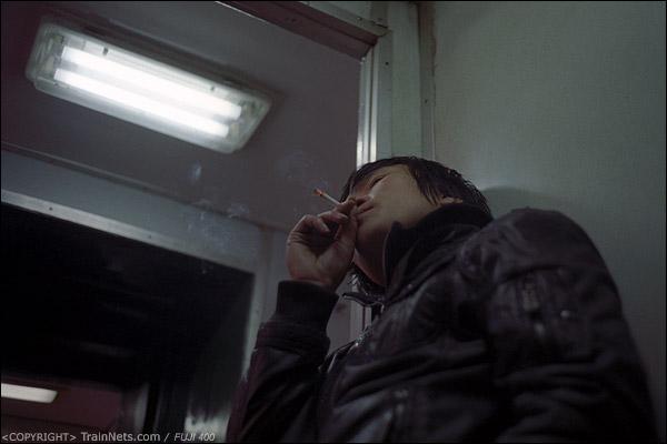 12号车厢门端,一位乘客点烟消磨时间。(D7427)