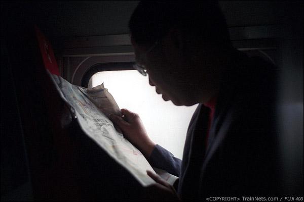 12号车厢,一位坐在洗手台上的乘客借着窗户的光看报纸。(D7432)