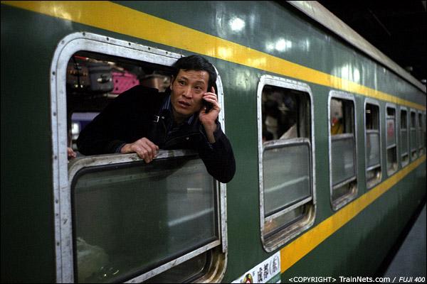 2013年1月30日。深圳站。凌晨,深圳开往成都的L76次列车,一位乘客探出头给同伴打电话。(D7513)