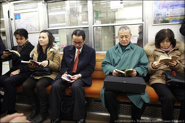 大阪地铁中央线。地铁上看书的乘客。日本地铁上不能打电话,而且玩手机的人也很少。(IMG-5038-120130)