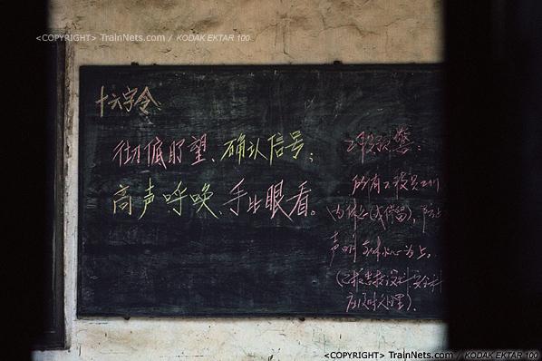 2013年8月10日。广州钢铁厂铁路。工业站旁的车库办公室,透过院子门口往内看,黑板上仍写有火车司机的操作规范。(E0334)