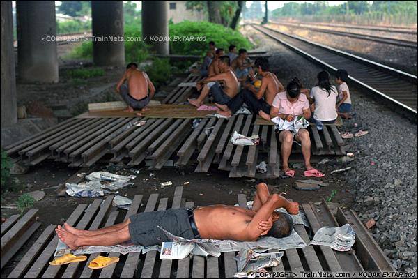 2013年8月11日。广州钢铁厂铁路,芳村花园旁的编组站,一旁工地的工人在桥下乘凉。(E0512)
