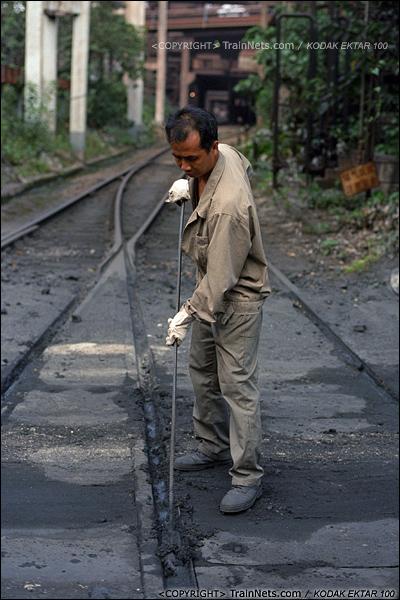 2013年8月11日。广州钢铁厂铁路,一名道口工在清理陷入路基的泥灰。(E0533)