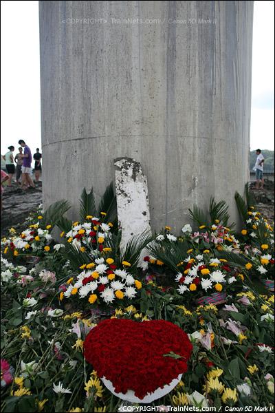 2011年7月28日。市民们自发前往事故现场鲜花纪念,一块列车的残骸被放在花丛中。(IMG-1160-110728)