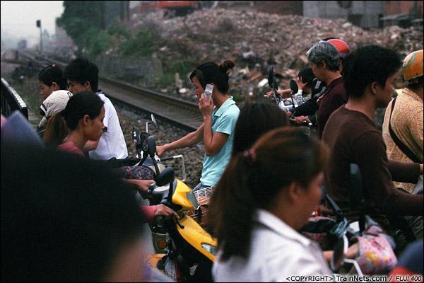 2013年5月6日。广西南宁长堽路六里道口。每当升起道闸,两侧人相交而过,十分拥挤。(D8504)