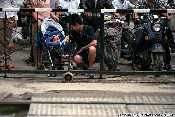 2013年5月6日。广西南宁长堽路六里道口。道口前,爸爸陪着宝宝等火车。(D8510)