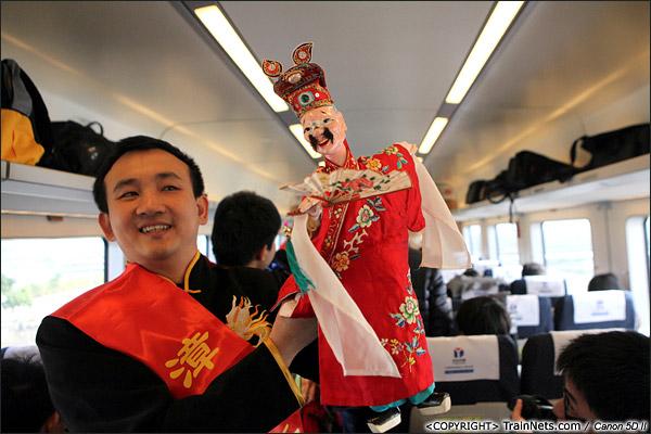 2013年12月28日。厦深铁路深圳北站首发的D2286次列车,一位福建的艺人在车上向大家表演布袋木偶戏。(IMG-6614-131228)