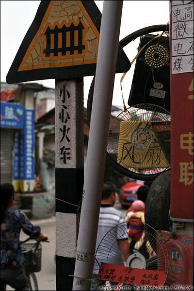 2013年5月6日。广西南宁长堽路六里道口。上班早高峰,通往道口的小路窄小,路旁的小店还蚕食着道路资源。(D8401)