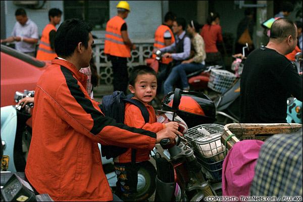 2013年5月6日。广西南宁长堽路六里道口。一位小孩经过道口还张望远处有无火车。(D8418)