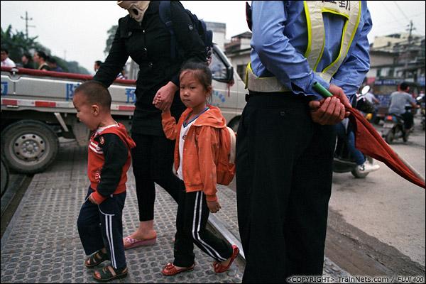 2013年5月6日。广西南宁长堽路六里道口。道口交通复杂,小孩通过也要牵紧。(D8430)