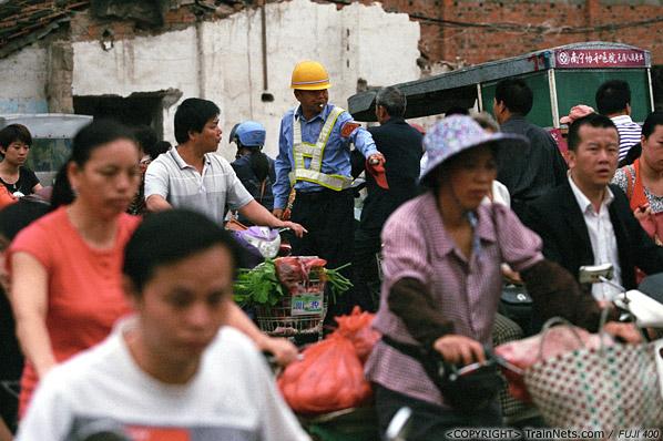 2013年5月6日。广西南宁长堽路六里道口。上班早高峰,道口工充当起了交警维护交通秩序。(D8520)