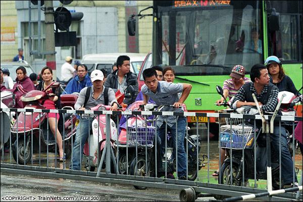 2013年5月6日。广西南宁明秀路道口。等候的时候久了,下班的市民焦急地张望火车何时到来。(D8627)
