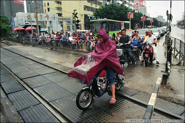 2013年5月6日。广西南宁明秀路道口。道闸一开,电动车像赛马一样冲出。(D8634)