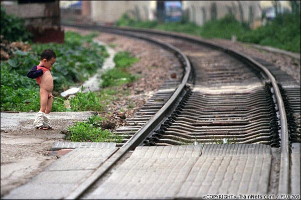 2013年5月6日。广西南宁虎邱道口。孩子调皮地在铁路旁撒尿。(D8712)