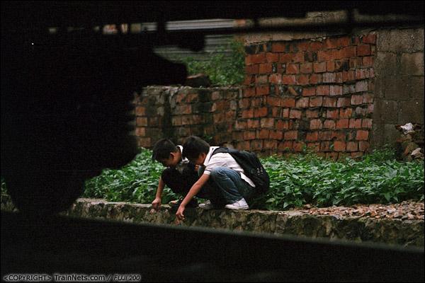 2013年5月6日。广西南宁明秀路道口南侧,放学的孩子在铁道上玩耍。(D8725)