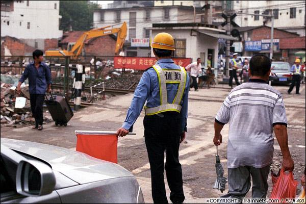 2013年5月6日。广西南宁长堽路六里道口。上班早高峰,道口工充当起了交警维护交通秩序。(D8402)