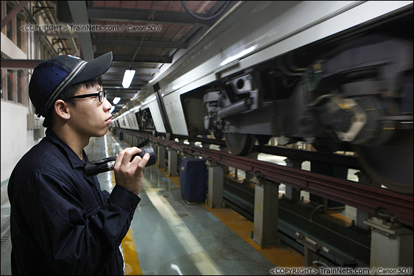 2014年1月17日。深圳动车所。列车入库,一名检修员目视检查转向架。(IMG-0866-140117)