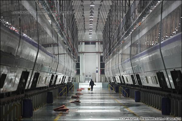 """2014年1月17日。深圳动车所。一名清洁工提着工具准备为动车""""洗澡""""。(IMG-1368-140117)"""